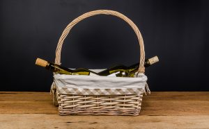 red wine bottles on wicker basket on wooden board and black background