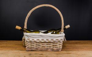 red wine bottles on wicker basket on wooden board and black background