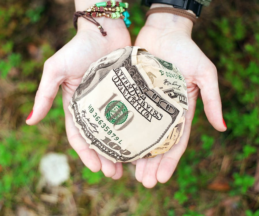 person holding money for donation