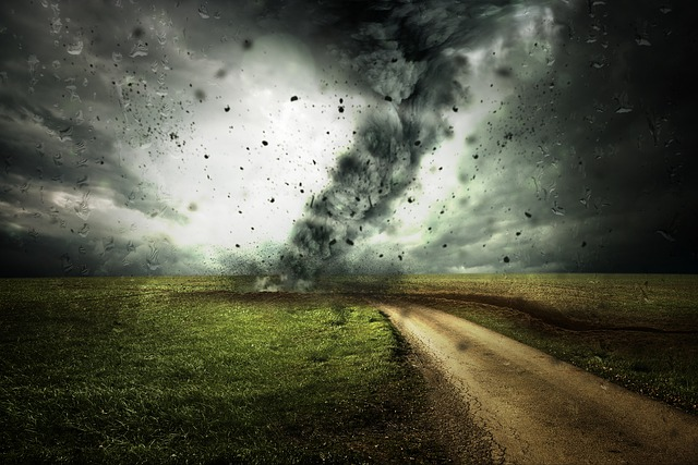 a hurricane running through an open field and causing dark sky