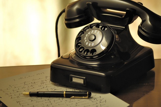 a vintage telephone with rotary beside a letter and a pen