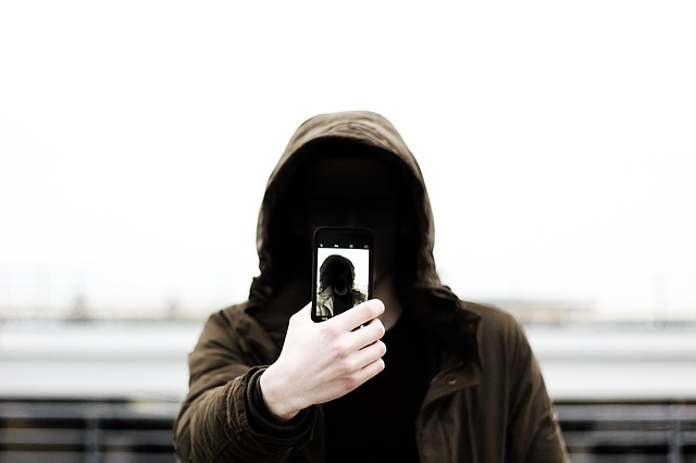 a man with a hood taking selfie