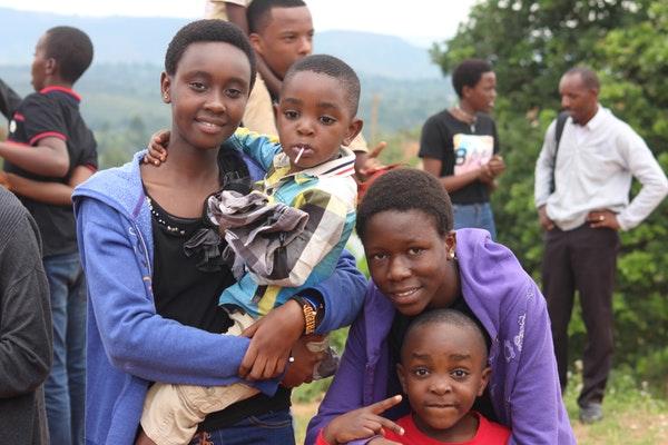 African woman wearing blue jacket carrying a little boy