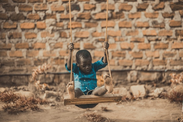 African boy wearing blue shirt sitting on swing