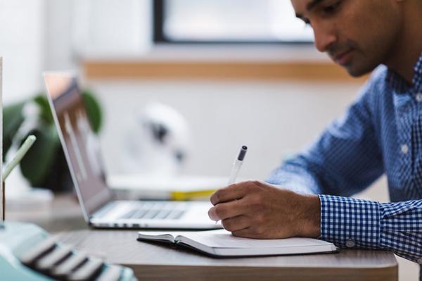 Man writing near a laptop